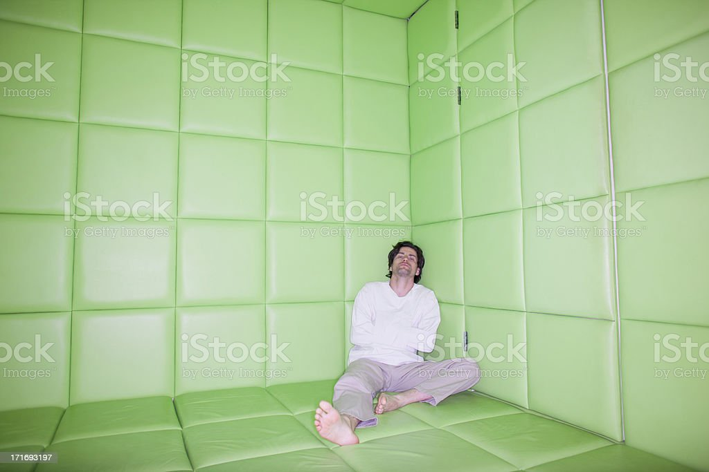 Man sitting with legs apart in padded room stock photo