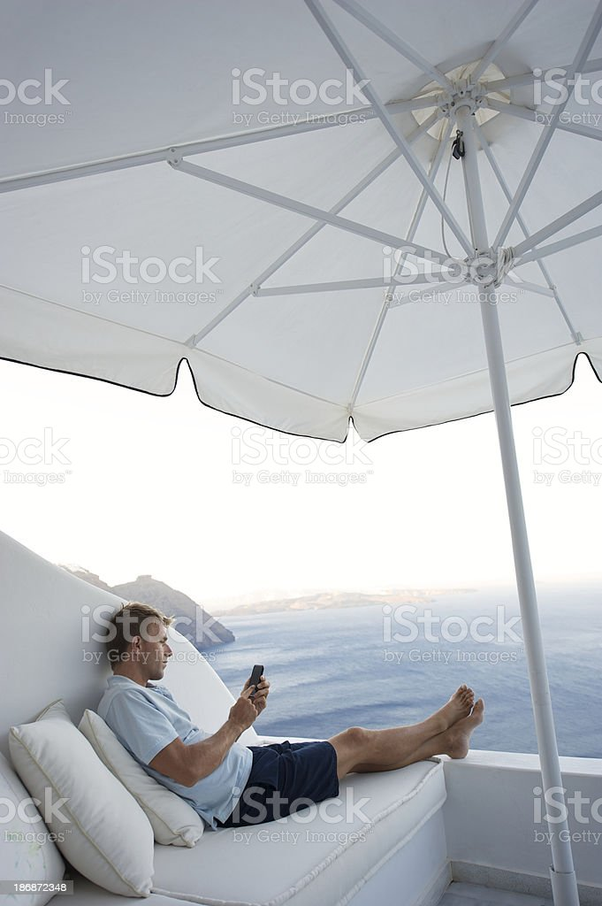 Man Sitting with Smartphone Texting Outdoors on Bright Seaside Balcony stock photo