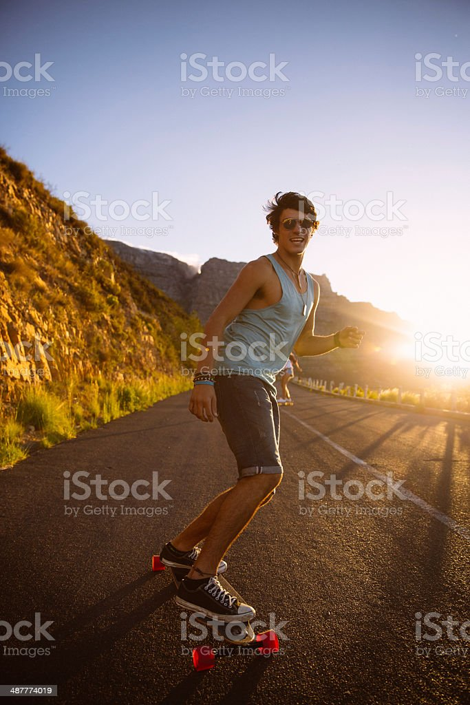 Man skating road longboard sunset stock photo