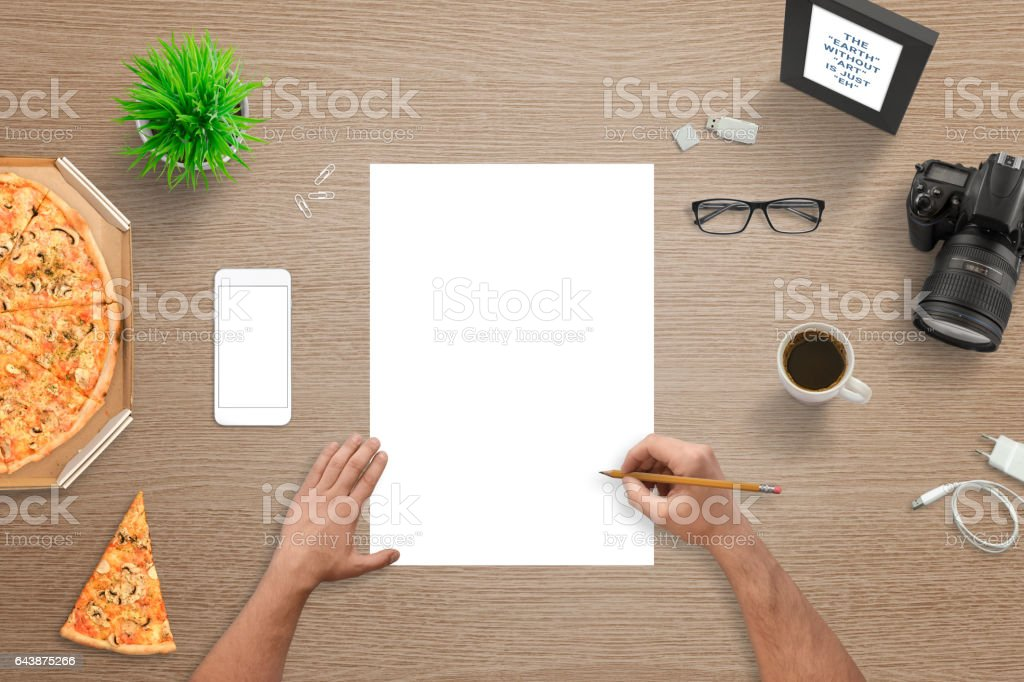 Man sketching on empty white paper. Top view of desk. White smart phone with blank screen for mockup. Digital camera, pizza, plant, glasses, coffee, photo frame beside. stock photo
