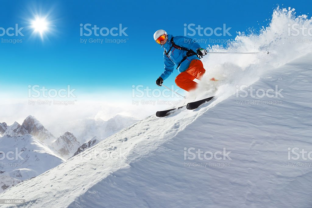 Man skier running downhill stock photo