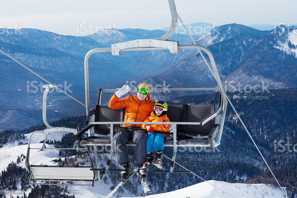Man skier with child lift on ropeway chair stock photo