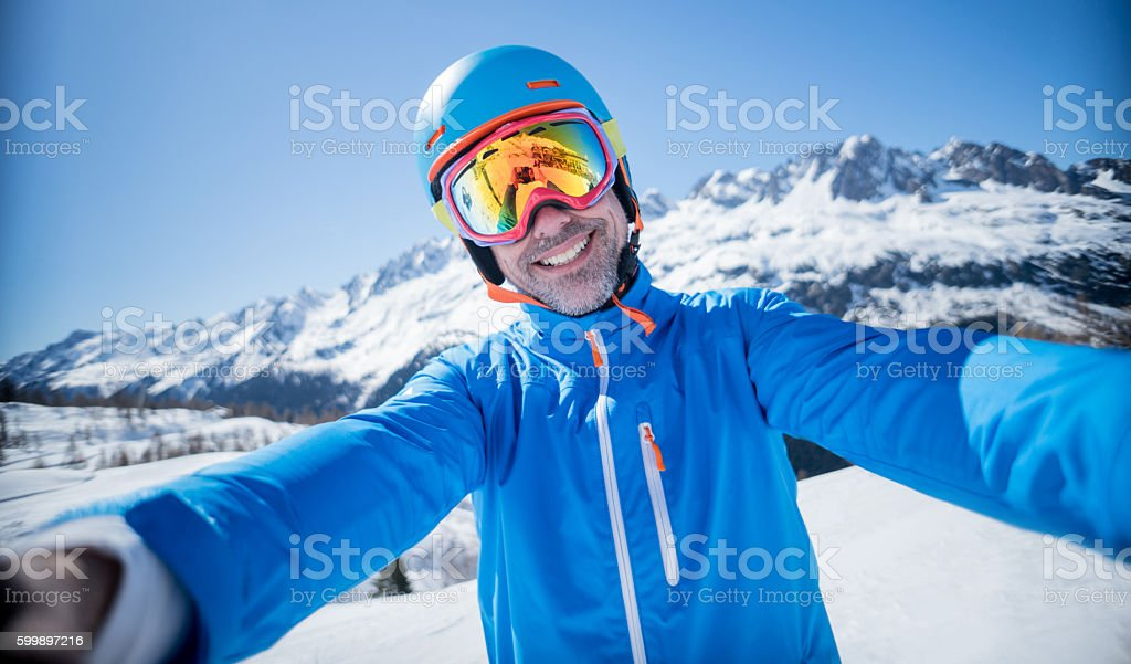 Man skiing and taking a selfie stock photo