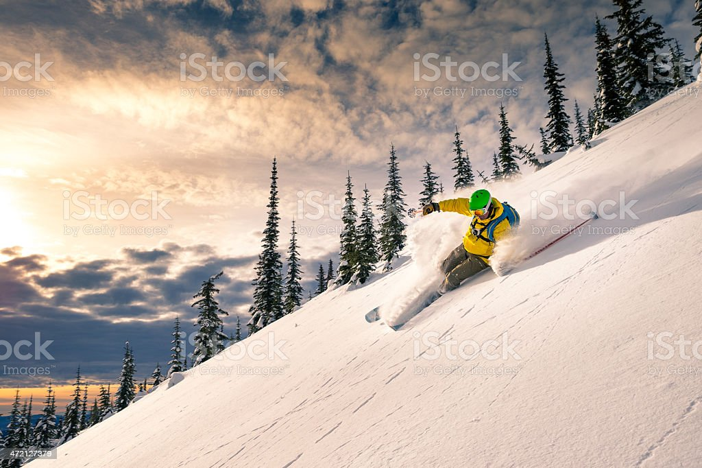 A man skiing down a powdery snow mountain stock photo