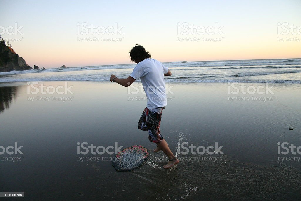 man skimboarding stock photo