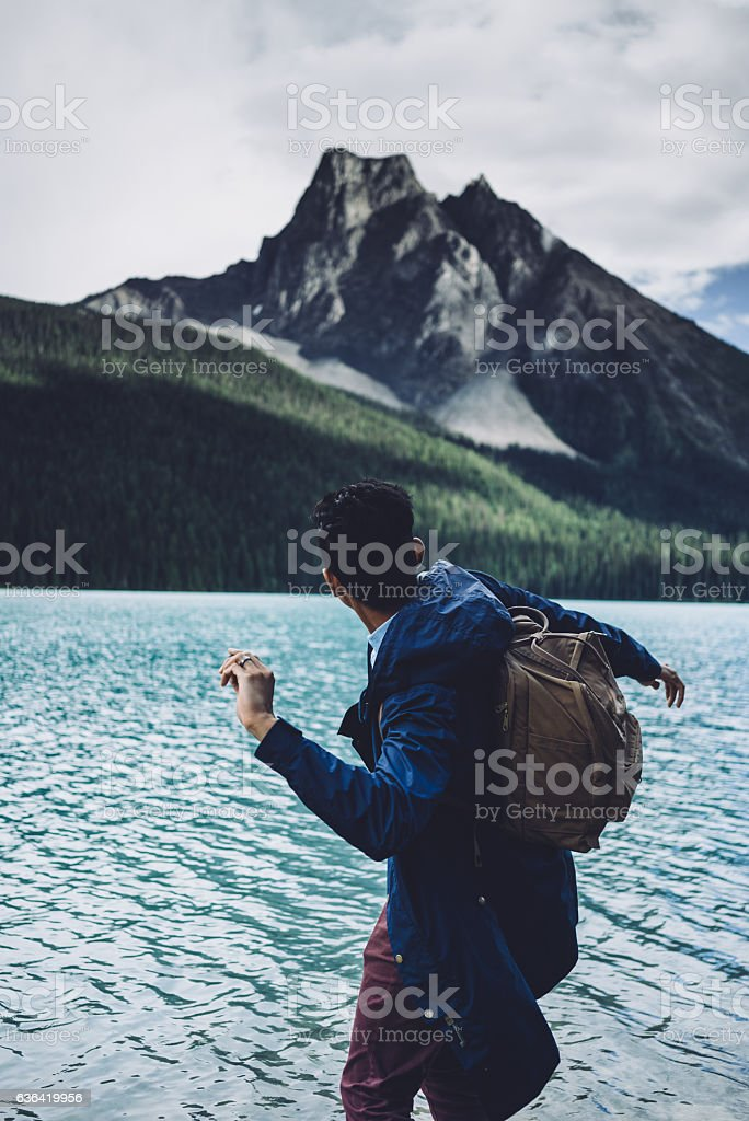 Man skipping rocks by a lake with mountains in background stock photo