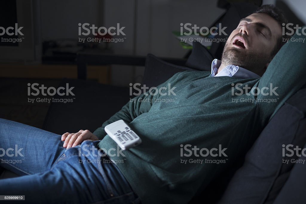 Man sleeping and snoring in front of television stock photo