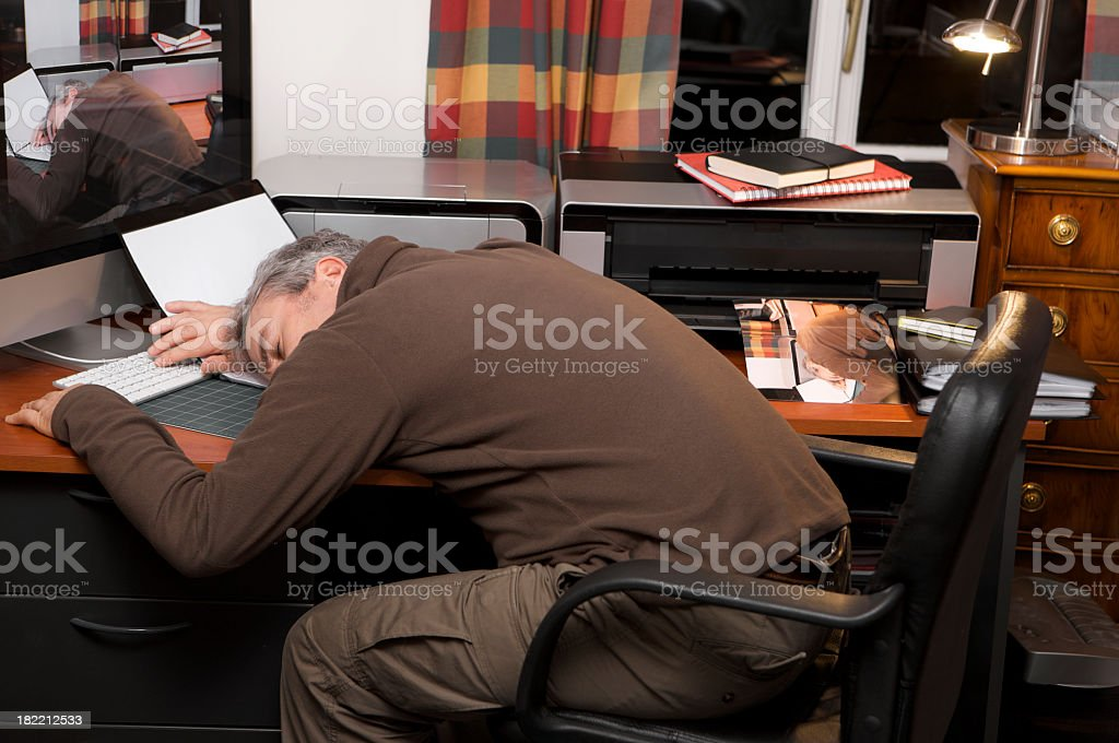Man sleeping at his home office desk late at night. stock photo