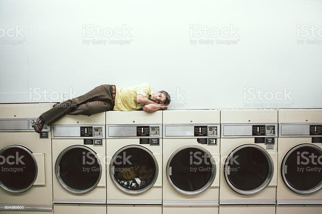 Man Sleeping at Laundromat stock photo