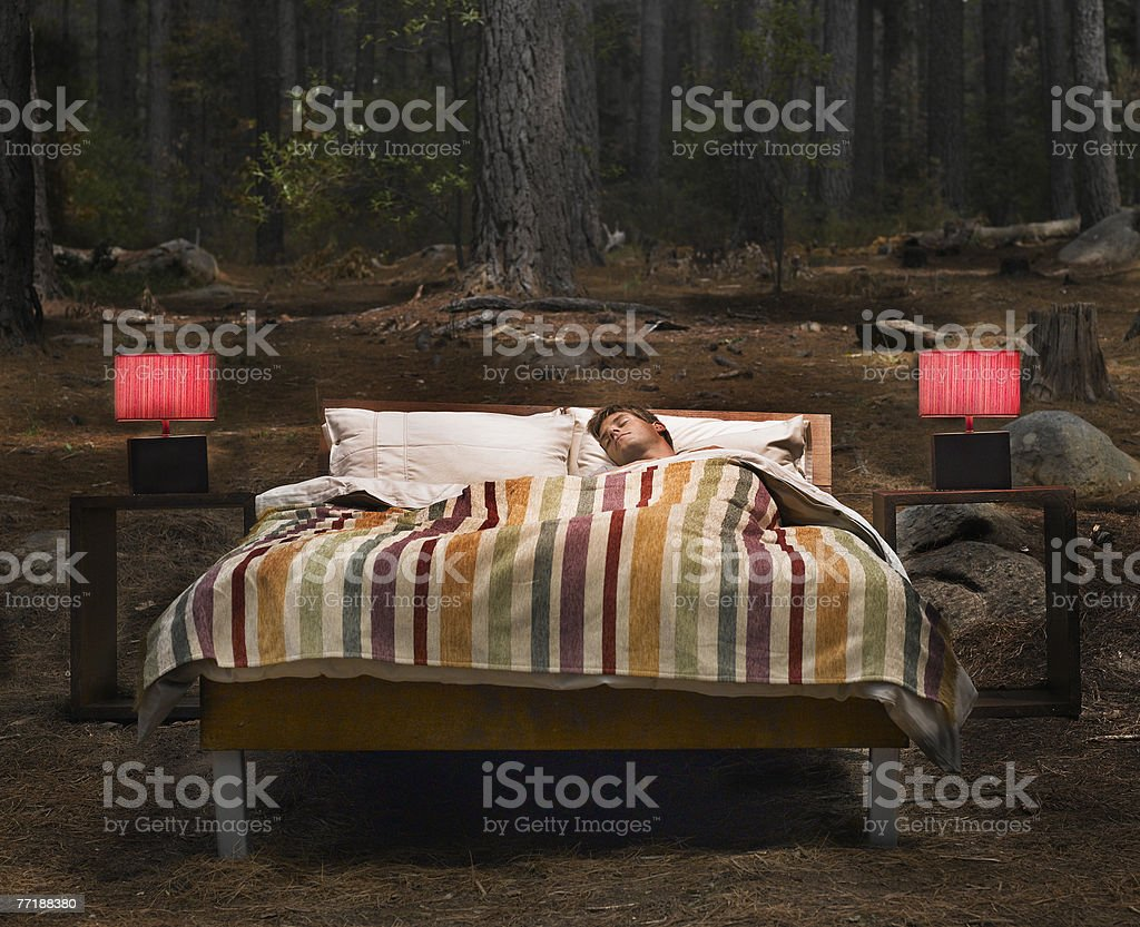 A man sleeping in a bed outdoors in the woods stock photo