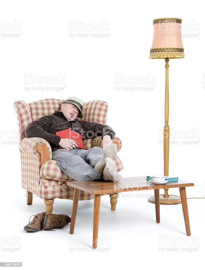 man sleeping in armchair while reading stock photo