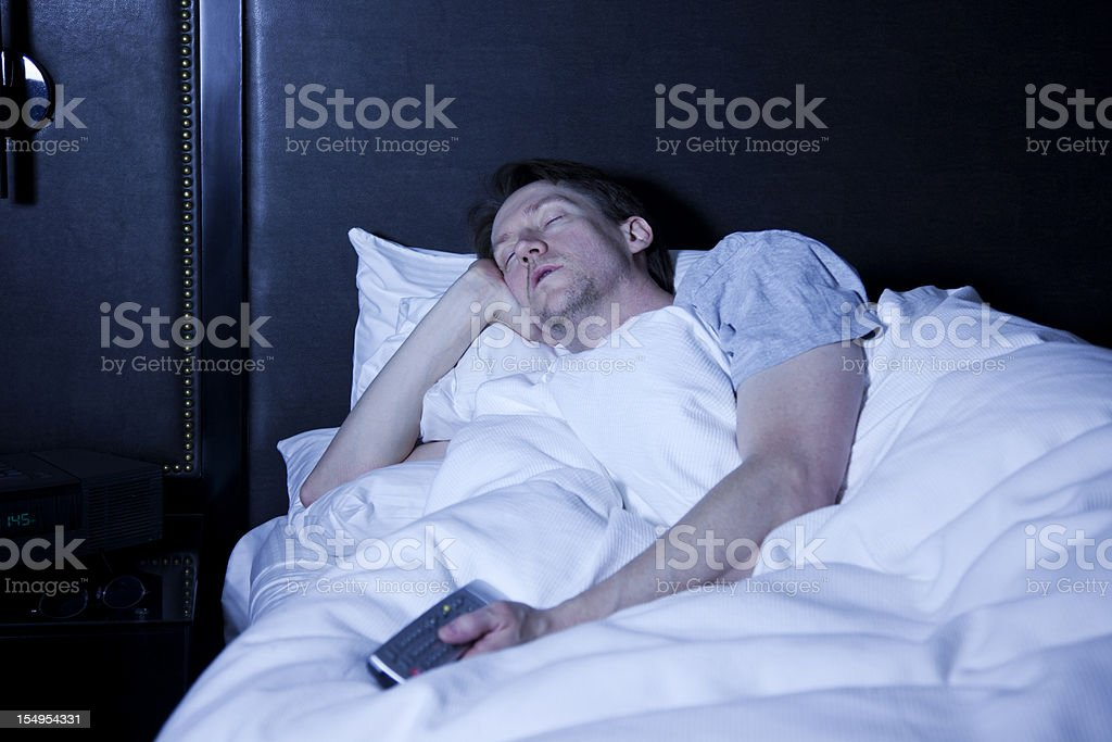 Man Sleeping in Bed with Television On stock photo