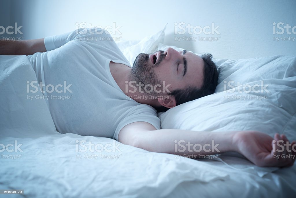 Man sleeping in his bed and snoring loudly stock photo
