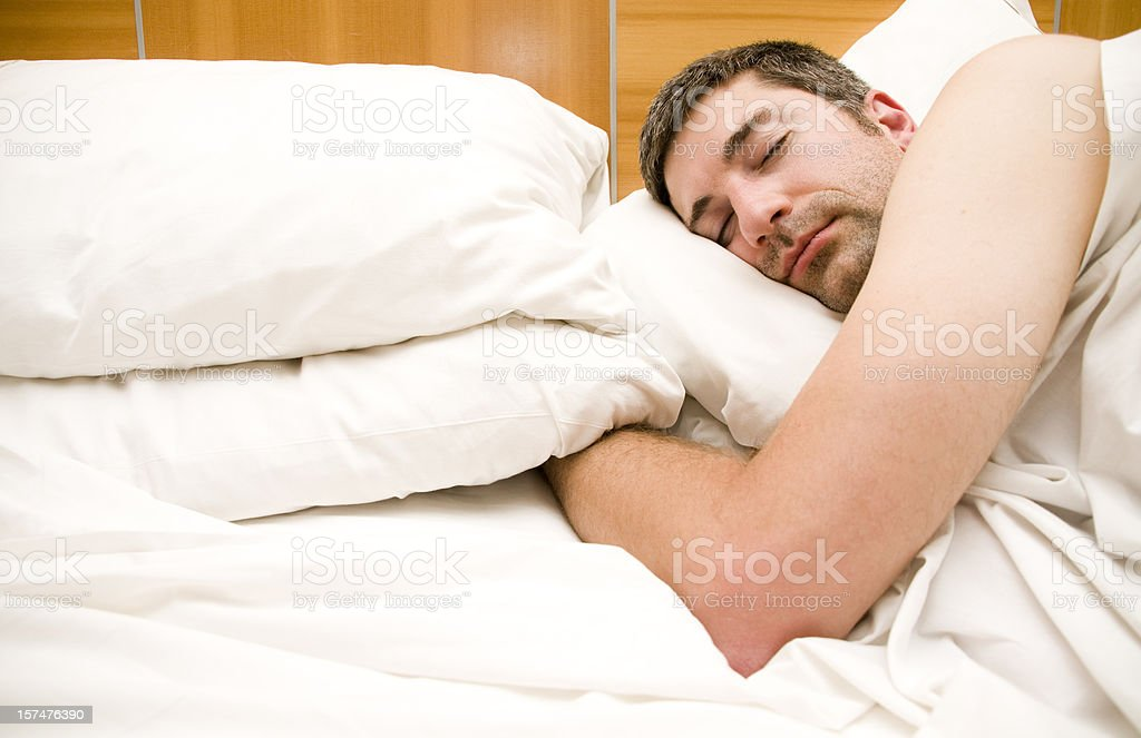 Man Sleeping in Hotel Bed royalty-free stock photo