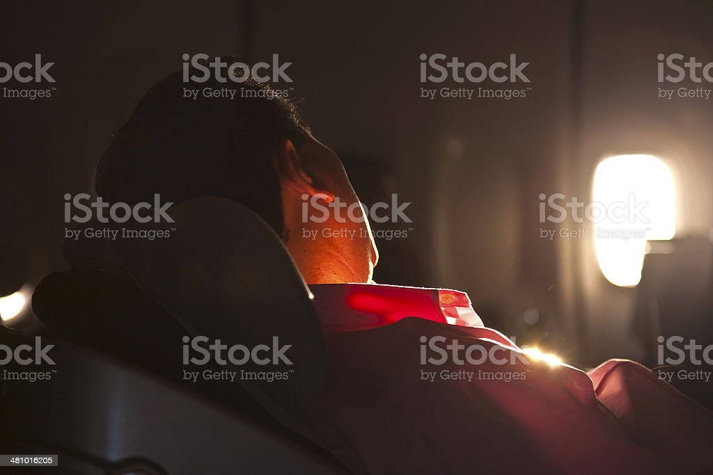 man sleeping in the seat of an aircraft in sunrise stock photo