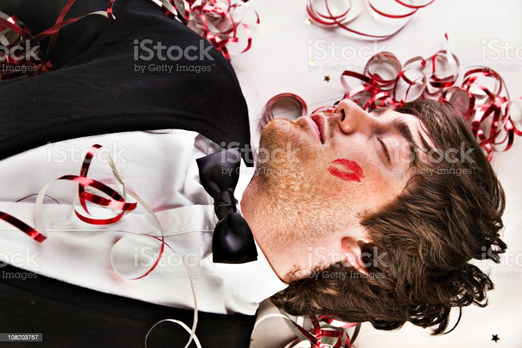 Man Sleeping on Floor at Party with Cheek Lipstick Print stock photo