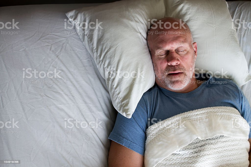 Man sleeping on his back in bed stock photo