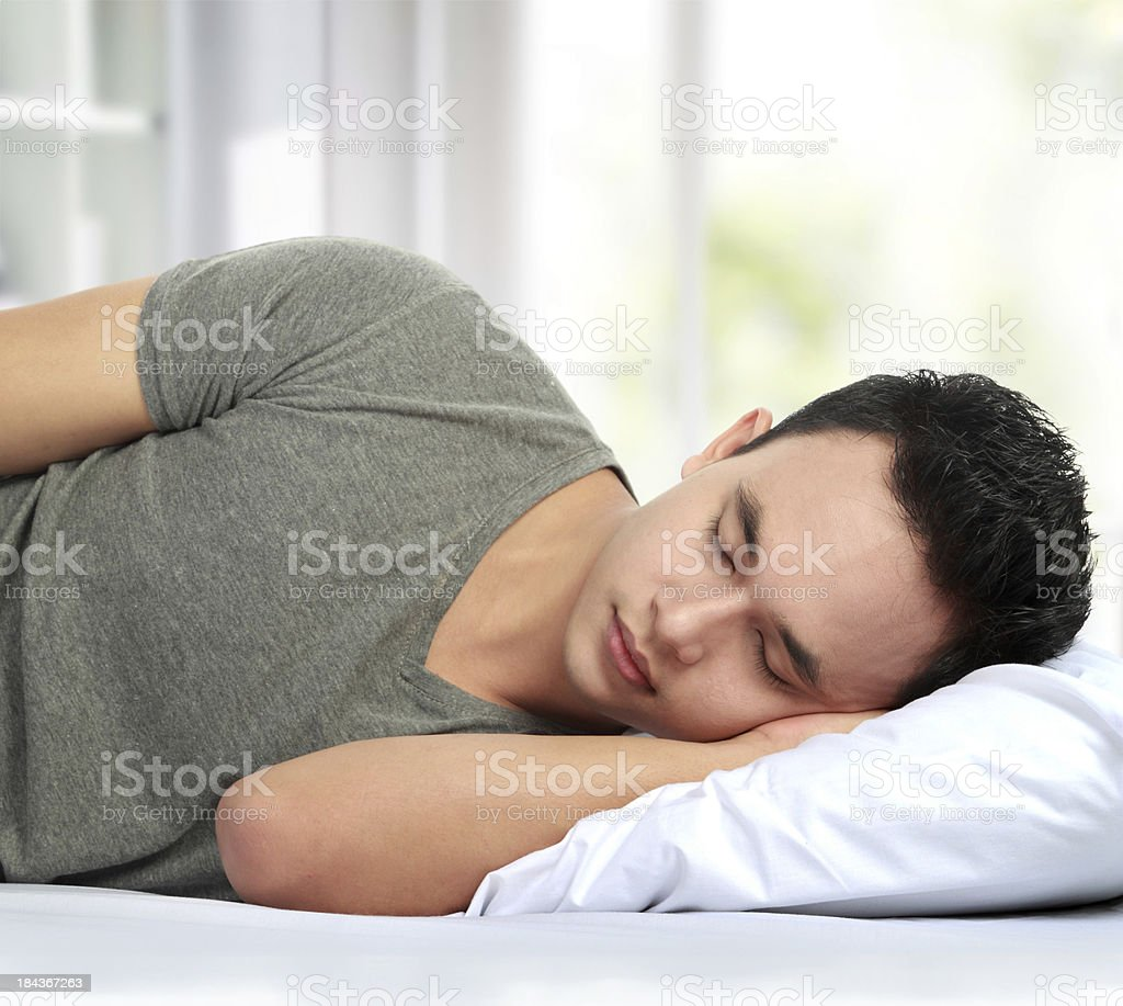 Man sleeping on his side in bed royalty-free stock photo