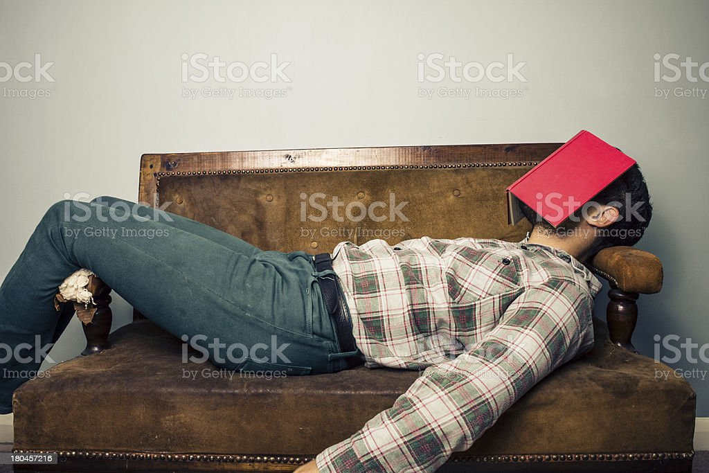 Man sleeping on old sofa with book covering his face royalty-free stock photo