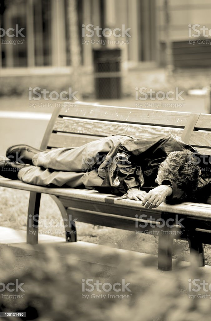 Man sleeping on park bench, black and white royalty-free stock photo