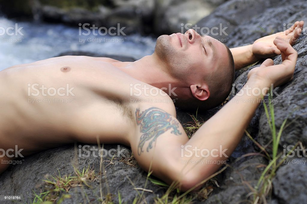 Man sleeping on rocks royalty-free stock photo