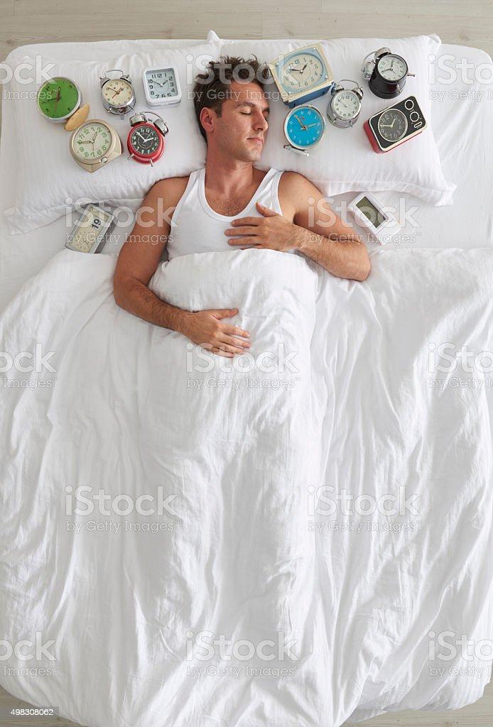 Man sleeping with lots of alarm clocks stock photo