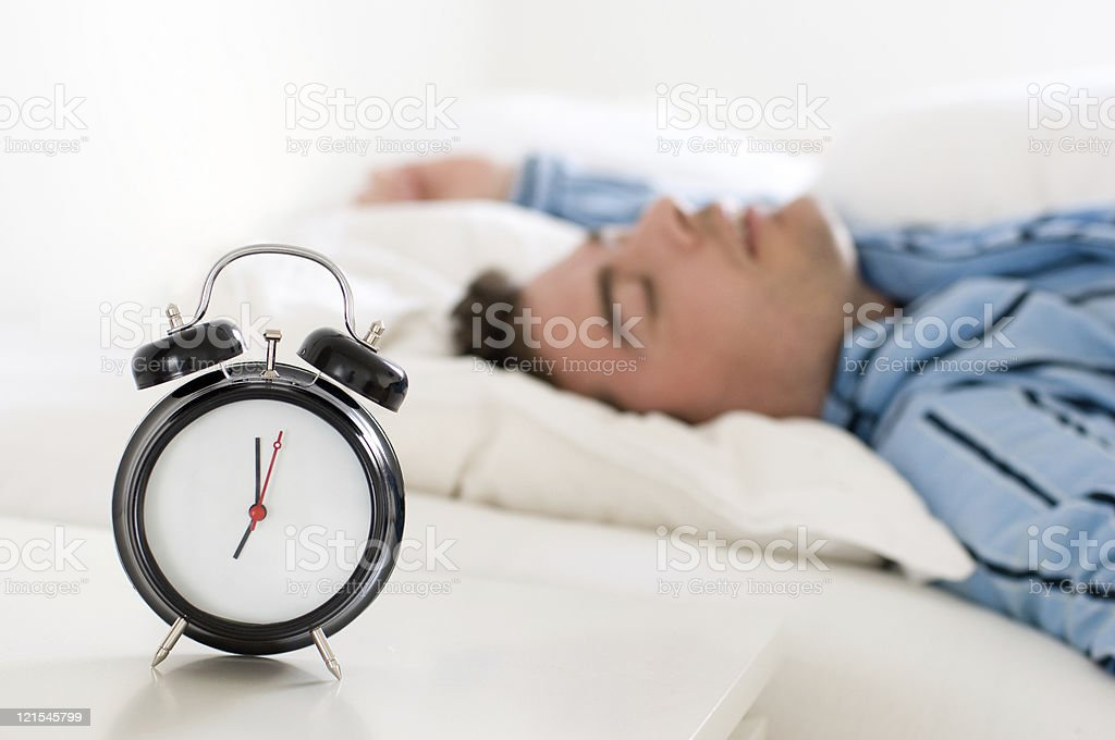Man sleeps even though it is time to get up royalty-free stock photo