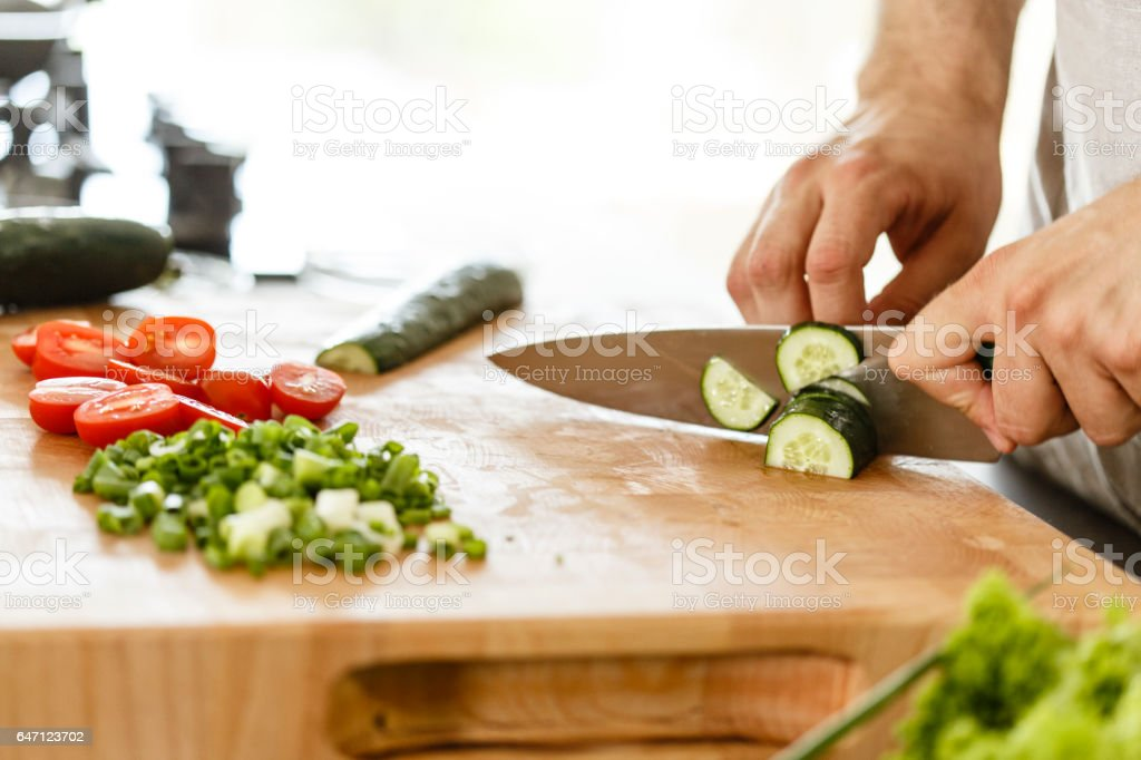 Man slicing cucumber stock photo