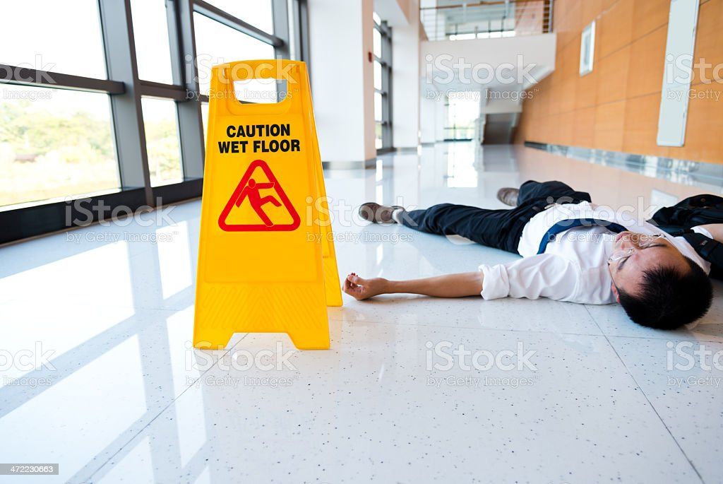 A man slipped on a floor next to a caution sign stock photo