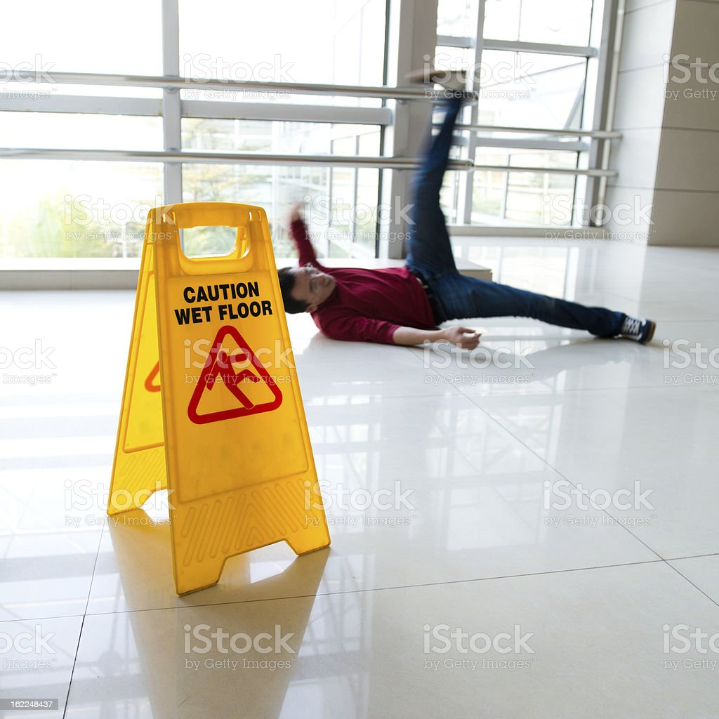 Man slipped on wet floor with wet floor sign nearby stock photo