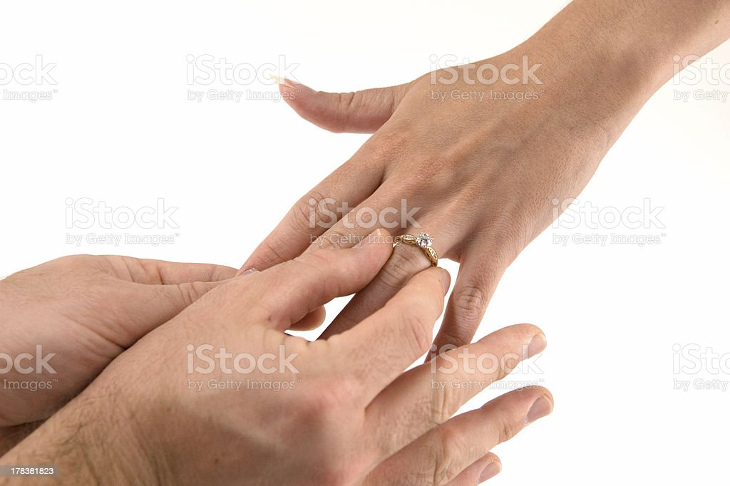 Man slipping engagement ring onto woman's finger royalty-free stock photo