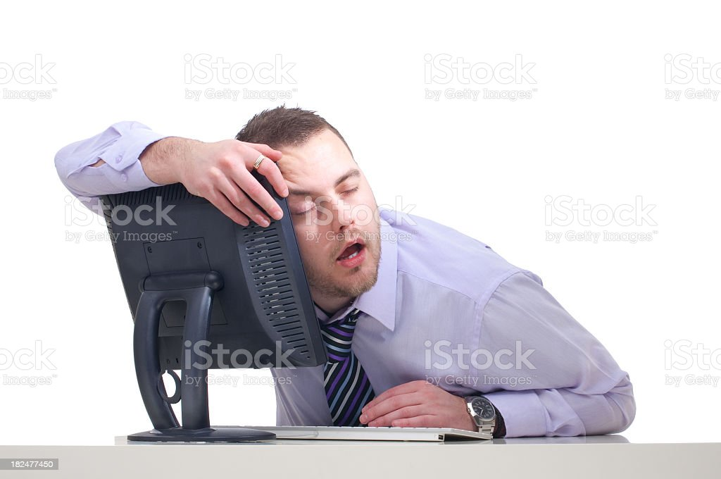 Man slouched over his computer monitor after a rough night stock photo