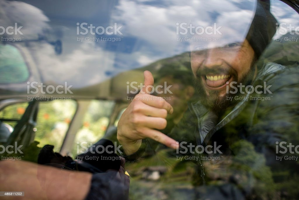 Man Smiles and gives Shaka sign through helicopter window stock photo