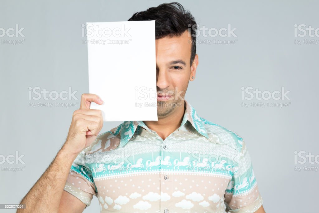 Man smiles and plays with the banner for advertising content. Handsome brazilian male wearing a colorful shirt. Summer, tropical. 30s. Fit and athletic. stock photo