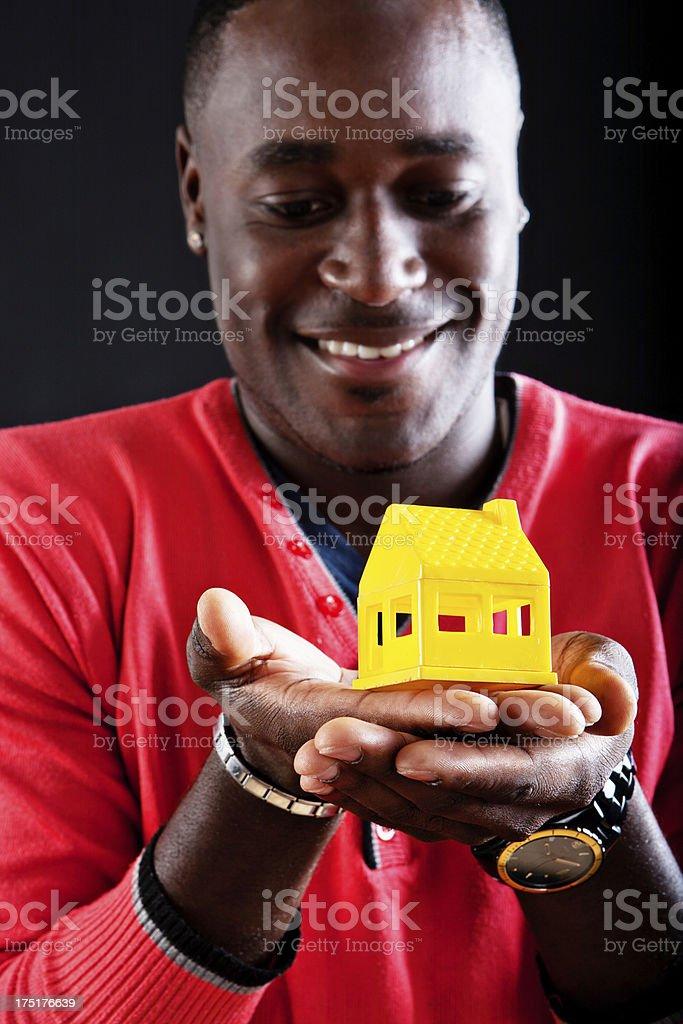 Man smiles down at yellow toy house stock photo