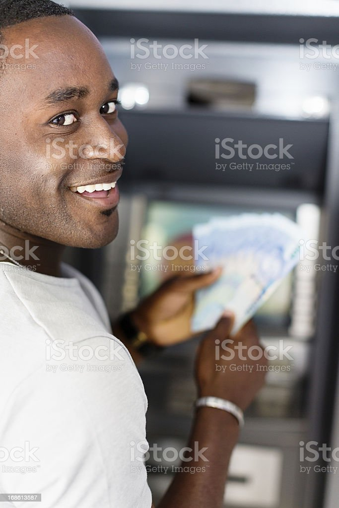 Man smiles over shoulder as he gets money from ATM stock photo