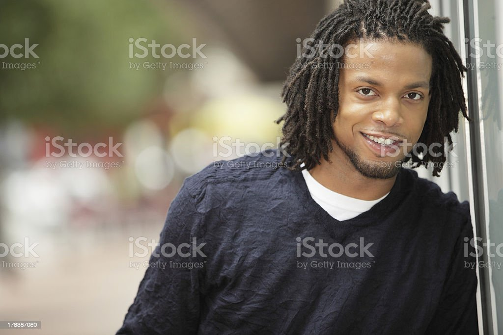 Man smiling and leaning on the wall stock photo
