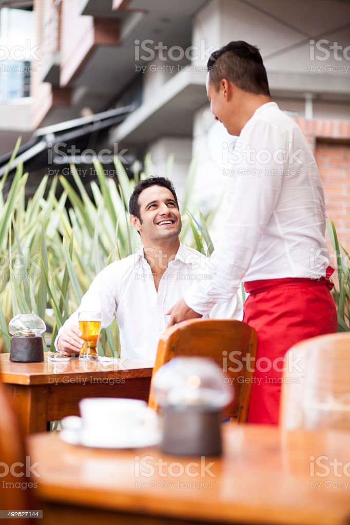 Man smiling and seeing the waiter stock photo