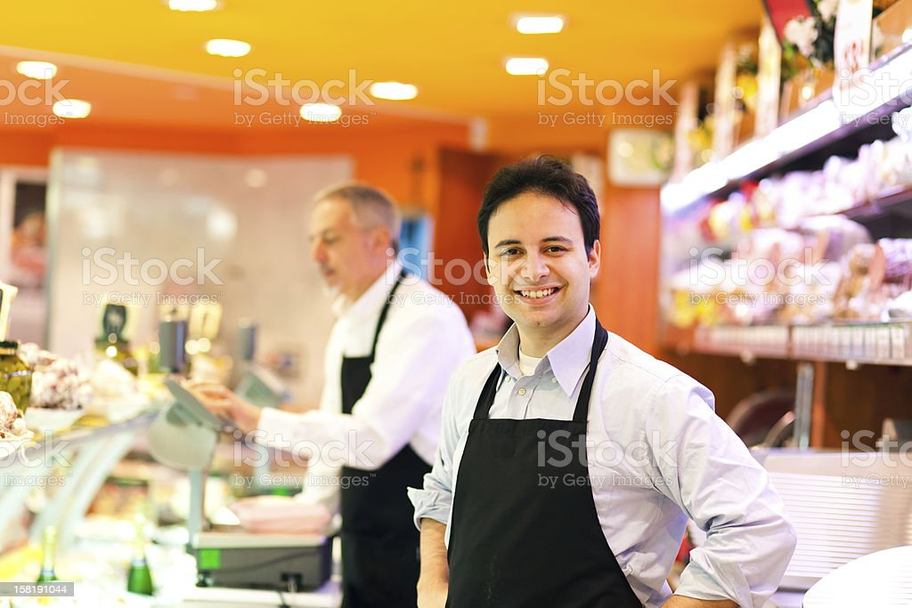 Man smiling at a camera while working at a grocery store royalty-free stock photo