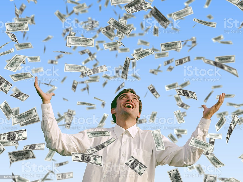 A man smiling while dollars fall from the sky stock photo
