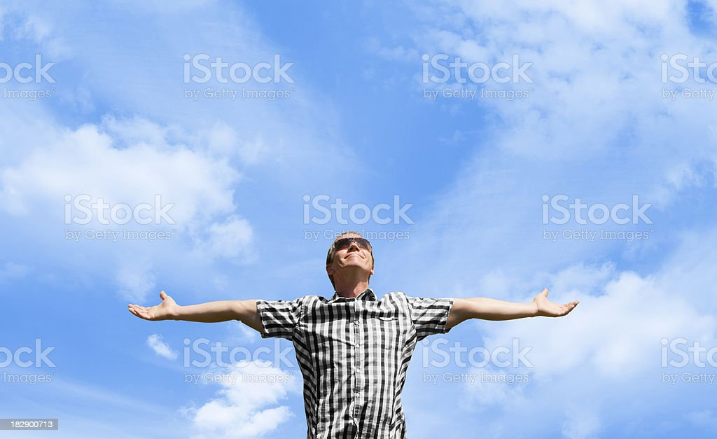 Man smiling with arms outstretched against blue sky royalty-free stock photo