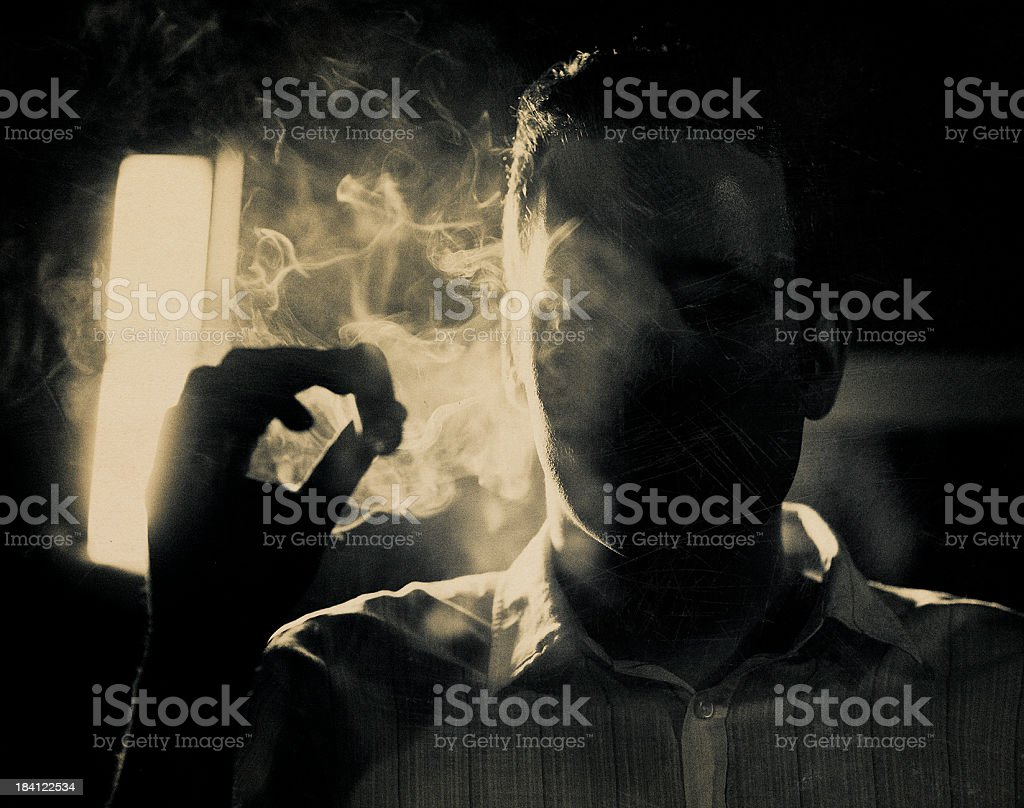 man smoking a cigar in the dark stock photo