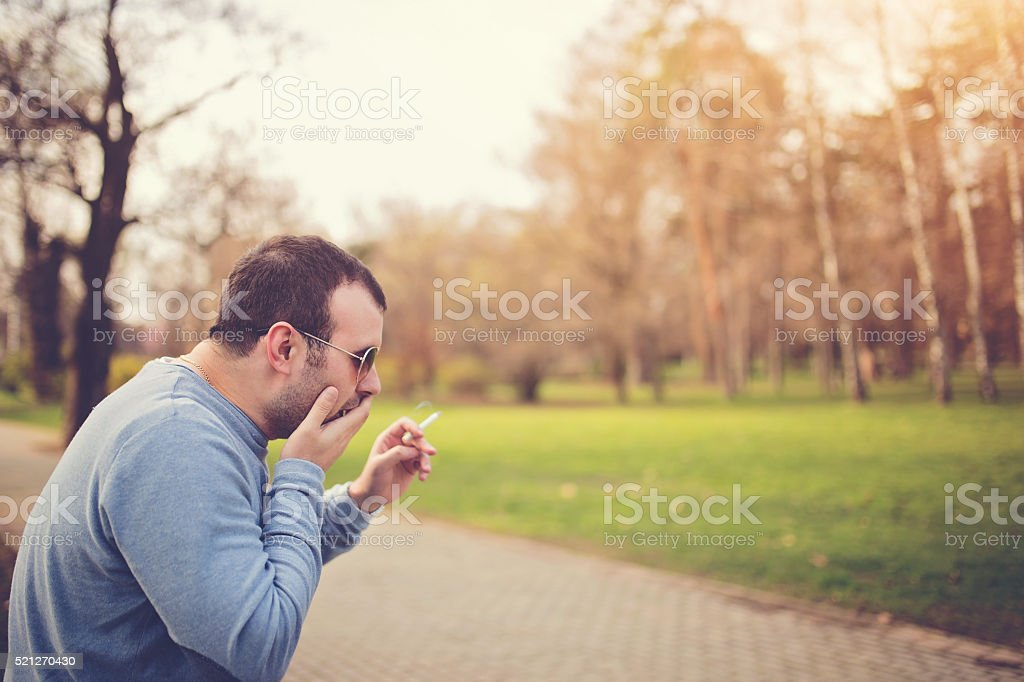Man smoking a cigarette and coughing stock photo