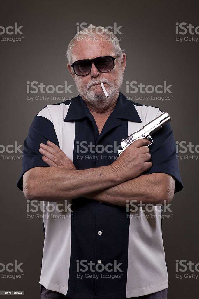 Man smoking a cigarette and holding handgun royalty-free stock photo