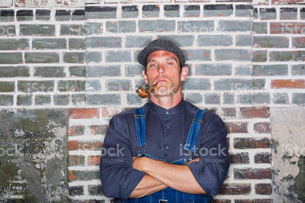Man smoking a pipe leaning against brick wall stock photo