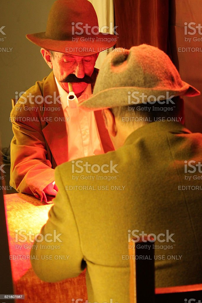 man smoking a pipe while playing cards with a friend stock photo