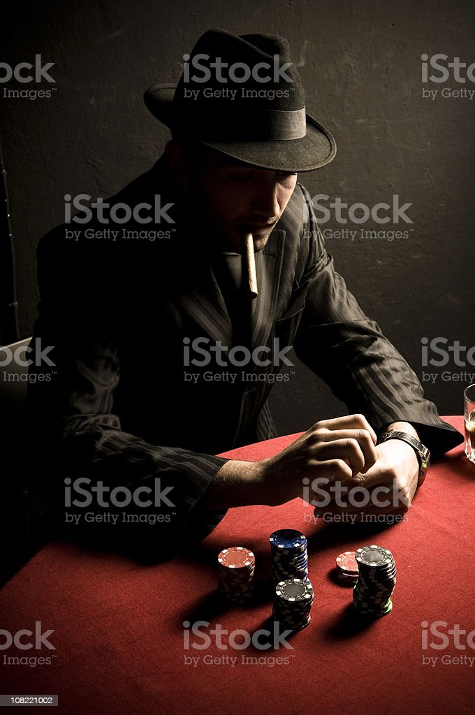 Man Smoking Cigar at Card Table with Poker Chips royalty-free stock photo