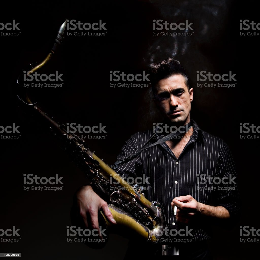 Man Smoking Cigarette and Holding Saxophone on Black Background stock photo