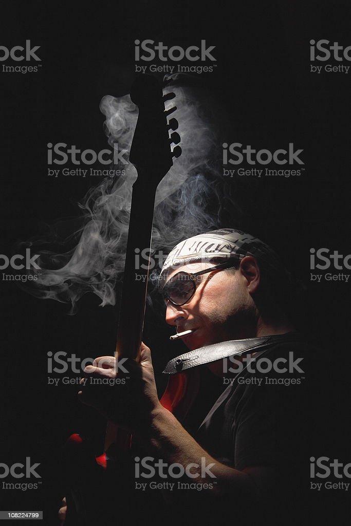 Man Smoking Cigarette and Playing Guitar, Low Key stock photo