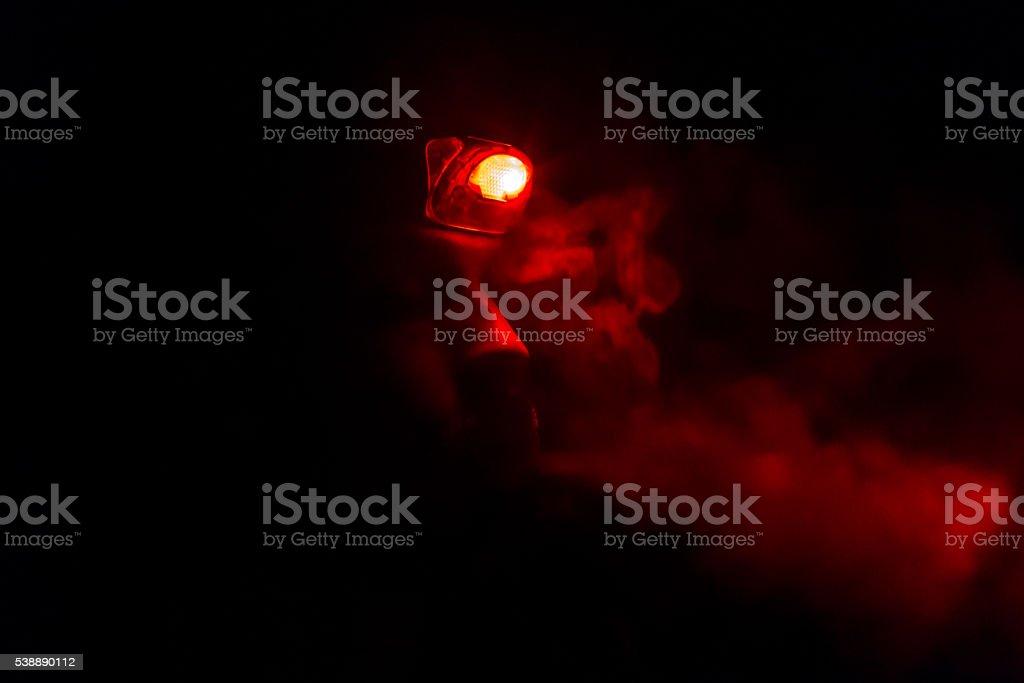 man smoking cigarette in pitch black night stock photo